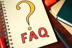 FAQ written on a notebook. Stock Photography