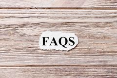 FAQS of the word on paper. frequently asked questions concept. Words of FAQS on a wooden background royalty free stock image