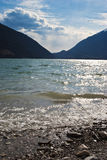 Far away... A sunny day on the beach of a lake with the mountains far away on the background royalty free stock image