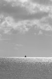 Far away. Single sailboat on the horizon Royalty Free Stock Photo