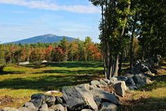 Far away Mountain. A far away Mountain on a warm Autumn day in New England , with warm foliage surrounding a lovely field wrapped with stones royalty free stock image