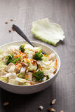 Far away shot of Asian Napa cabbage salad. Asian Napa cabbage salad with organic broccoli, almonds, chicken, and a rice vinaigrette on a dark wood background far Stock Photos