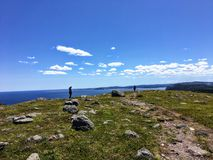 A far away shot of two males at the edge of a rocky headland or cliff overlooking the Atlantic Ocean on a sunny day hiking. Along the east coast trail outside stock image