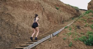A far away shot of the young woman in black sports gear , running up steps stock video footage