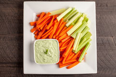 Far away top view of green dip with carrots and celery. Creamy radish kale green dip with carrots and celery far away top view Royalty Free Stock Images