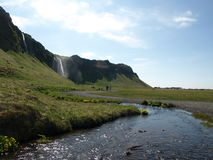 Far- Away Waterfall and a Stream. Beautiful waterfall, with a stream glinting in the Icelandic sun lying in the foreground Stock Images