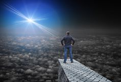 Far bright star illuminates the darkness, and the man standing above the clouds Stock Images