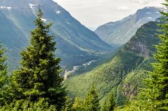 A River Runs Through a Deep Wooded Valley Below in Glacier National Park. Far down in the green timber laden valley a river makes its way through the wilderness stock photos