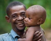 Far med ett barn från en stam av pygméer Arkivfoto