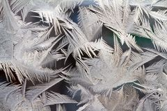 Frost draws patterns on a windowpane. Frost draws abstract ice background patterns on a windowpane. Russia Royalty Free Stock Image