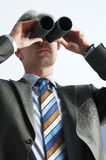 Far-seeing businessman. One businessman is looking trough field-glasses Stock Image