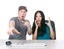 Far too shocking. A young men and girl looking shocked while sitting at desk using a computer Stock Image