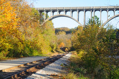 Far train under bridge. A passenger train rounds a curve and approaches under a high arch bridge in a scenic area Stock Photo