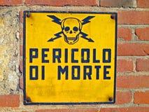 Fara av död undertecknar med skallen och korslagda benknotor som är skriftliga i Itali royaltyfri bild