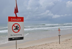 Fara och varning undertecknar längs strand beklär Arkivfoto