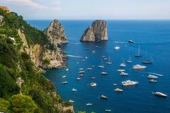 Faraglioni di Capri. Faraglioni of Capri, in south italy with many boats in front of them stock photo