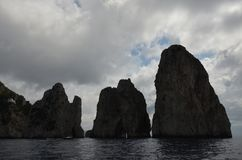 Faraglioni, rock, coastal and oceanic landforms, sea, sky. Faraglioni is rock, sky and cloud. That marvel has coastal and oceanic landforms, promontory and stack Stock Images