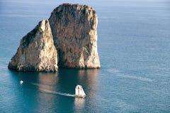 Faraglioni rocks. Sailing ship crossing the Faraglioni rocks. Island of Capri, Italy stock photos