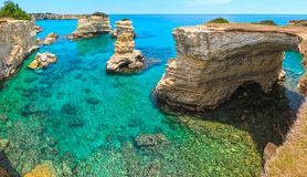 Faraglioni at Torre Sant Andrea, Italy. Picturesque seascape with cliffs, rocky arch and stacks faraglioni, at Torre Sant Andrea, Salento sea coast, Puglia Stock Photos