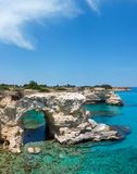 Faraglioni at Torre Sant Andrea, Italy. Picturesque seascape with cliffs, rocky arch and stacks faraglioni, at Torre Sant Andrea, Salento sea coast, Puglia Royalty Free Stock Images