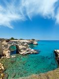 Faraglioni at Torre Sant Andrea, Italy. Picturesque seascape with cliffs, rocky arch and stacks faraglioni, at Torre Sant Andrea, Salento sea coast, Puglia Royalty Free Stock Photo