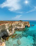 Faraglioni at Torre Sant Andrea, Italy. Picturesque sunshiny seascape with cliffs, rocky arch at Torre Sant Andrea, Salento sea coast, Puglia, Italy. Two shots Stock Images