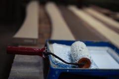 Farba rolownik błocący z białą farbą w błękitnym zbiorniku zdjęcie stock