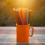 Farbbleistift auf Skizzenbuch und hölzerner Tabelle der Weinlese im Sonnenuntergang Stockfoto