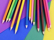 Farbbleistifte auf mehrfarbigem Papier Stockfotos
