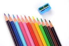 Farbbleistifte mit Bleistiftspitzer auf weißem Hintergrund Lizenzfreie Stockfotografie