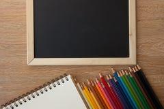Farbbleistifte mit Notizbuch und Tafel Lizenzfreie Stockfotografie