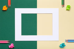Farbbleistifte mit Rahmen auf grünem und gelbem Hintergrund Lizenzfreie Stockfotos