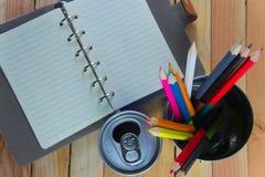 Farbbleistifte und -notizbuch auf Holztisch sehen auf Draufsicht stockfotografie