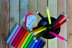 Farbbleistifte und -notizbuch auf Holztisch sehen auf Draufsicht Stockfoto