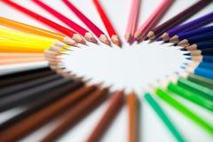 Farbbleistifte vereinbart in einer Herzform Stockbilder