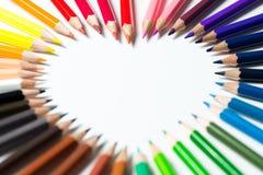 Farbbleistifte vereinbart in einer Herzform Stockbild