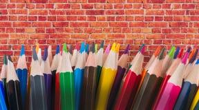 Farbbleistifte von verschiedenen Farben und von Backsteinmauer Lizenzfreie Stockfotografie