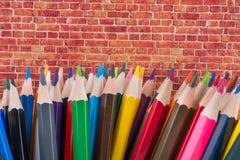 Farbbleistifte von verschiedenen Farben und von Backsteinmauer Stockfotografie