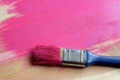 Farbe-bedeckter Malerpinsel auf gemaltem Holz Stockfotos