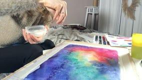 Farbe der erwachsenen Frauen mit farbigem Aquarell malt und besprüht Salz schafft Effekt in einer Kunstakademie stock video footage