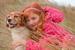 Farbe des horizontalen Formats schoss vom roten behaarten Mädchen mit rotem behaartem Hund, Gisborne, Neuseeland Lizenzfreies Stockfoto