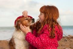 Farbe des horizontalen Formats schoss vom roten behaarten Mädchen mit rotem behaartem Hund, Gisborne, Neuseeland Stockfotos