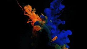Farbe im Wasser auf einem schwarzen Hintergrund Die Tinte im Wasser löst sich auf Eine Wolke der orange und blauen acrylsauerfarb stock footage