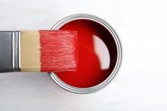Farbe kann und Bürste auf hölzernem Hintergrund stockfotos