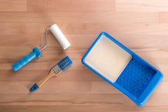 Farbe-Rolle, Farbe und Bürste auf Holztisch Stockfotografie