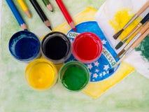 Farben, Bürsten, Bleistifte und und beflecktes Gewebe auf dem Brasilien-fla Stockbilder