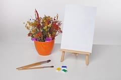 Farben, Bürsten, Blumen und ein Blatt Papier auf einem Gestell Lizenzfreies Stockfoto