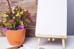 Farben, Bürsten, Blumen und ein Blatt Papier auf einem Gestell Stockfotos