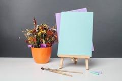 Farben, Bürsten und ein Blatt Papier auf einem Gestell Lizenzfreies Stockfoto