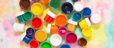 Farben, Bürsten und Palette auf dem bunten Hintergrund stockbilder